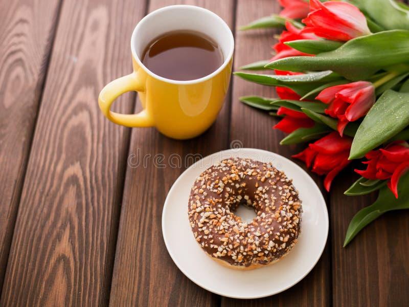 Ciambella sul piatto bianco con i tulipani e la tazza rossi di tè su un fondo di legno marrone Prima colazione nell'ora legale, v fotografia stock