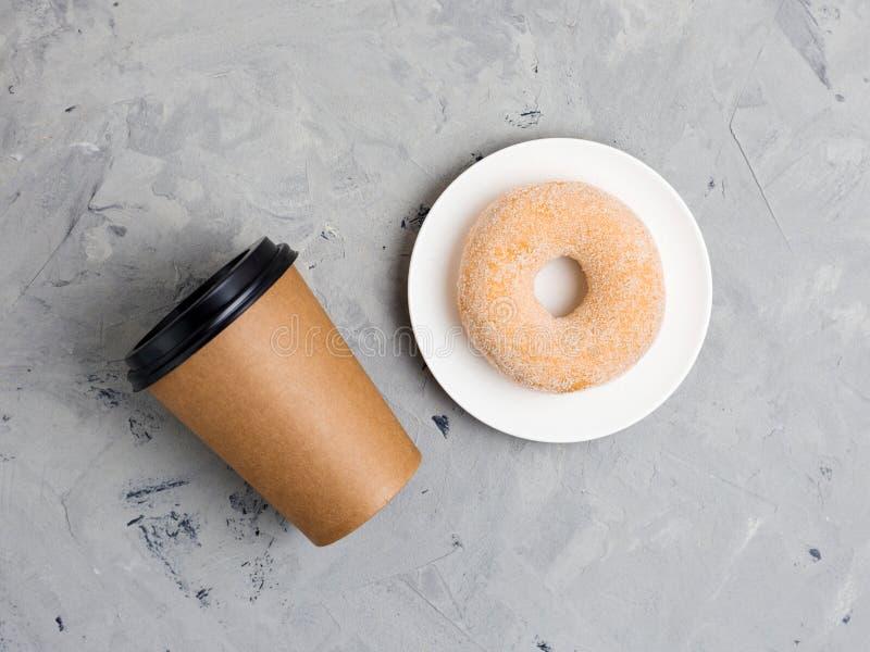 Ciambella variopinta dello zucchero e tazza di carta marrone su fondo concreto grigio, fine su, vista superiore Concetto del forn fotografia stock