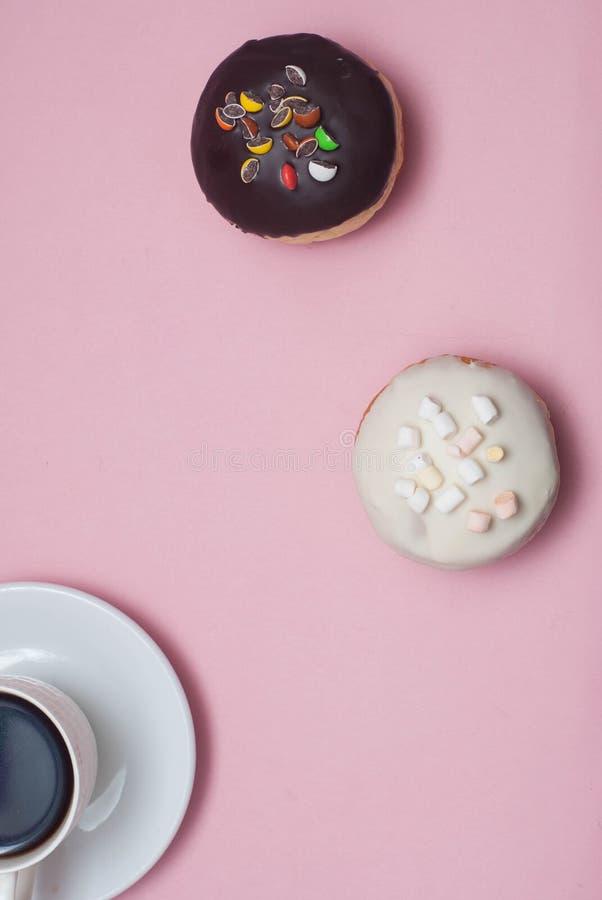 Ciambelle di vista superiore con cioccolato e glassa e tazza di caffè bianche, sul fondo di rosa pastello Guarnizioni di gomma pi fotografia stock