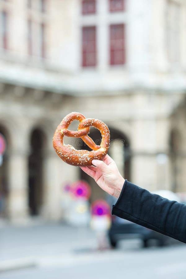 Ciambellina salata salata nelle mani di un uomo su fondo dell'opera di Vienna immagini stock libere da diritti