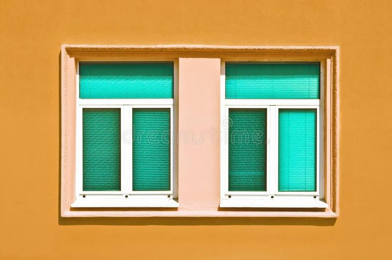 Ciano finestre sulla parete gialla fotografia stock