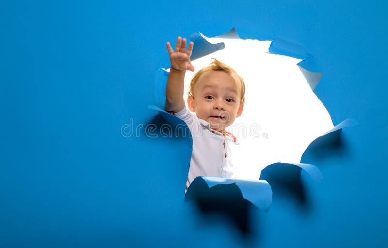 Ciao l? Entrata a nuova vita o inizio Sguardo curioso del bambino del ragazzo dal foro in carta Bambino che taglia da parte a par immagine stock libera da diritti