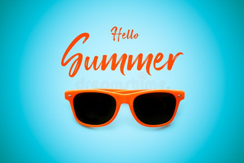 Ciao messaggio di testo arancio di estate e risiedere piano degli occhiali da sole dell'arancia nel fondo blu intenso Concetto pe fotografia stock libera da diritti