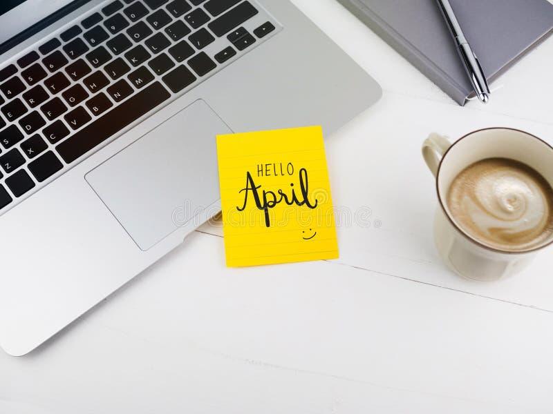 Ciao scrittura della mano di aprile sulla nota appiccicosa sullo scrittorio del lavoro immagini stock