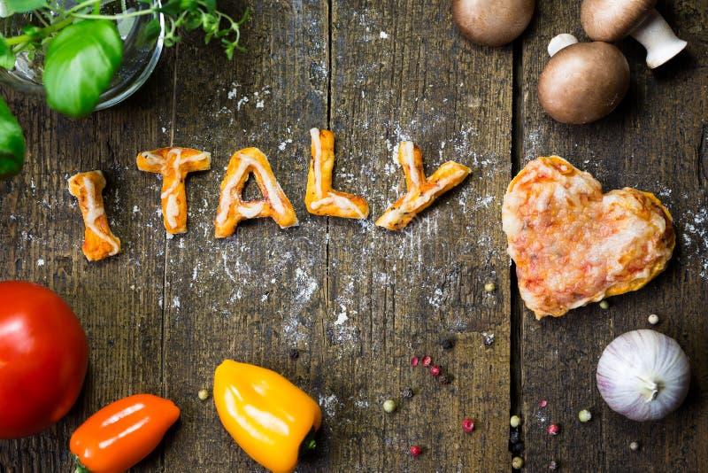Ciast warzywa na nieociosanym drewnianym stole i listy, słowo Italy obrazy royalty free