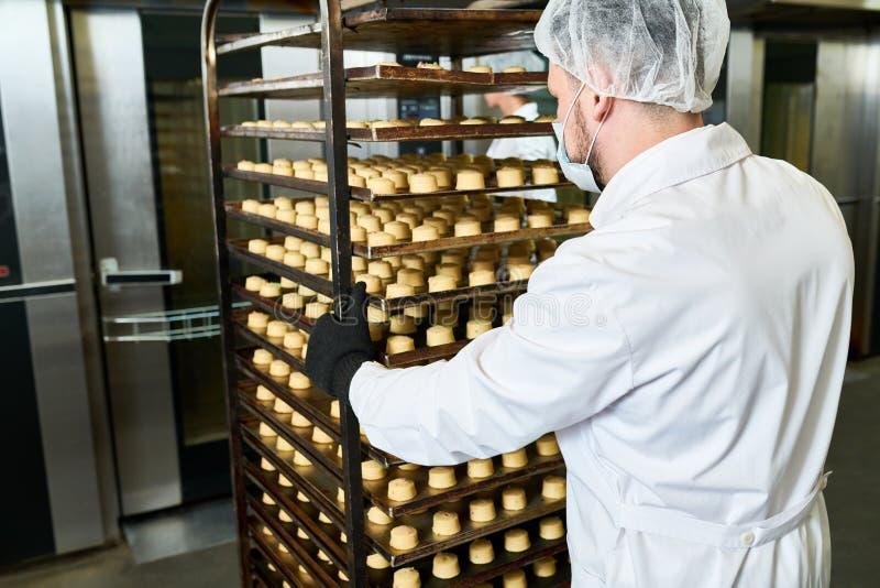 Ciasteczko pracownika fabrycznego dosunięcia tac stojak z ciastem zdjęcie royalty free