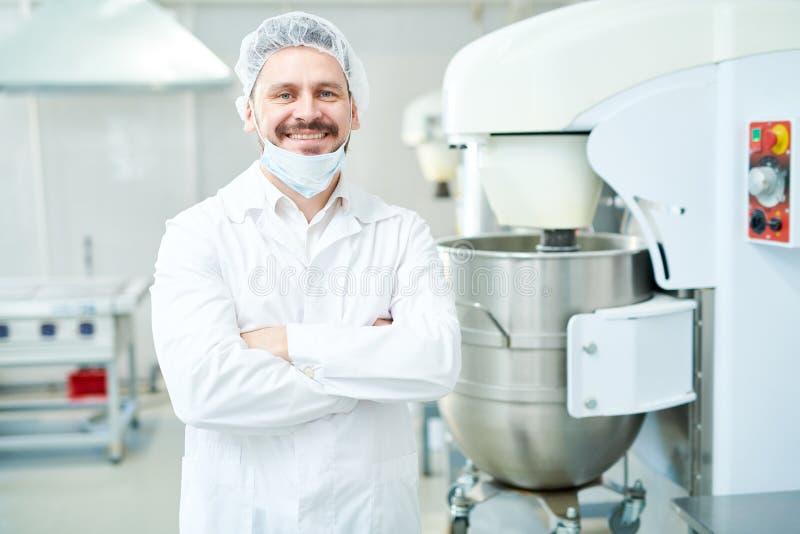 Ciasteczko pracownika fabrycznego ono uśmiecha się i pozycja fotografia stock
