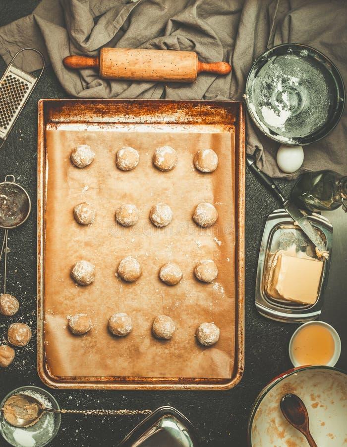 Ciastka ciasto na wypiekowej tacy, przygotowanie na kuchennym stole z opłatami drogowa i składniki, obrazy royalty free