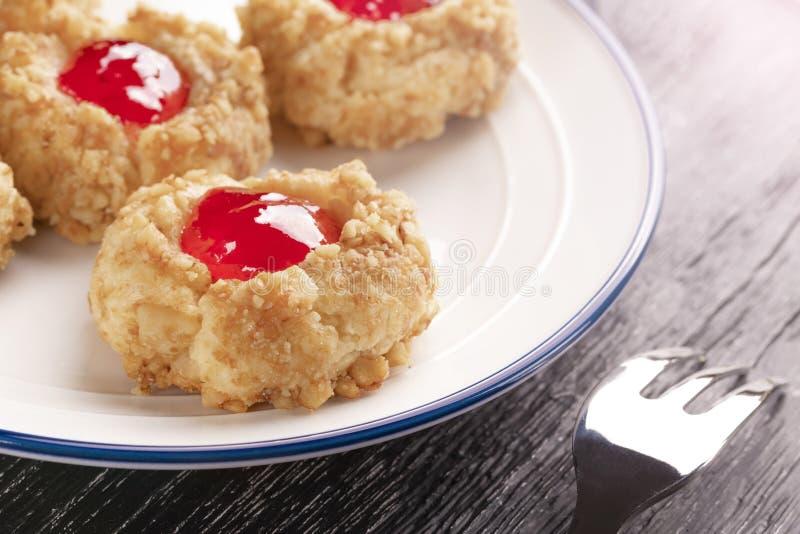 Ciastka robić od hazelnut shortcake z truskawkowym dżemem wśrodku białego talerza z wzorzystym deserowym rozwidleniem dalej obraz stock