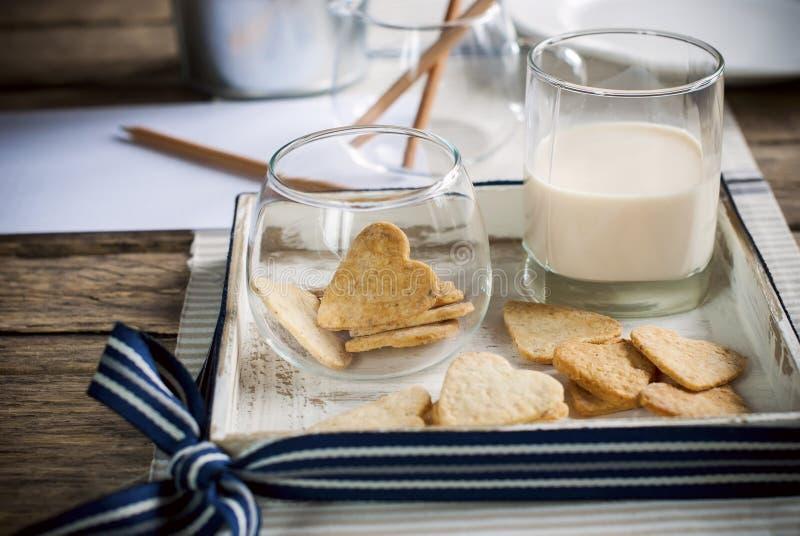 Ciastka w formie serc z mlekiem na Drewnianym stole zdjęcia stock