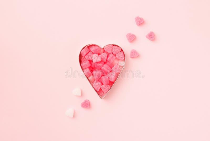 Ciastka w kształcie serca z konfetti na różowym tle pastelu Karta Concept Valentine Widok z góry, ilość miejsca na tekst obraz stock