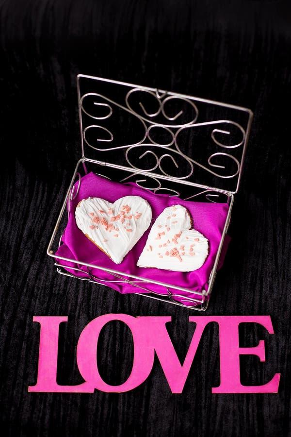 Ciastka w postaci kierowych kłamstw w szkatuły wpisowej miłości w górę fotografia stock