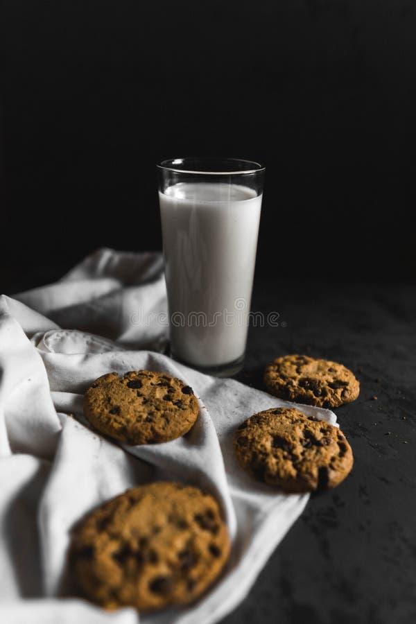 Ciastka z czekoladowymi statkami i mlekiem z ciemnym tłem fotografia stock