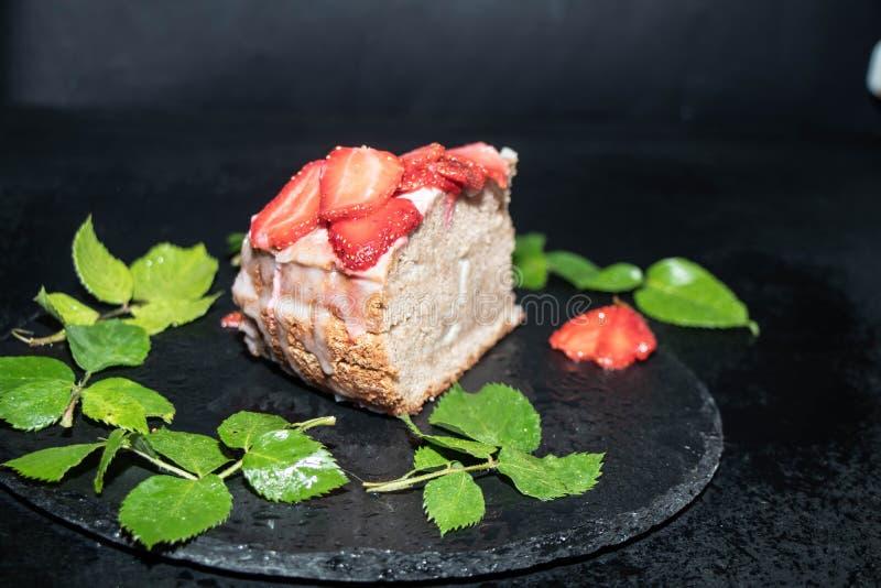 Ciastko tort z kwaśną śmietanką dekorował z truskawkami, świeża jagoda na tacy z błękitnymi światłami w tle, obraz royalty free