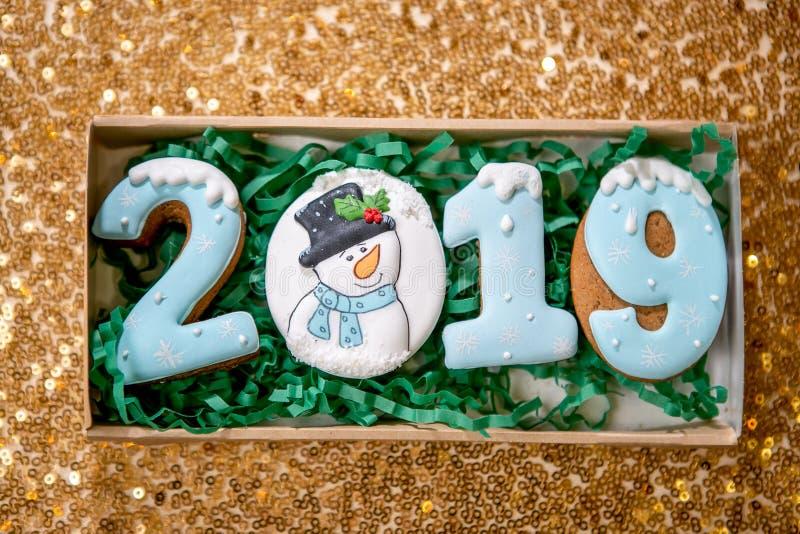 Ciastko w postaci liczb 2019 w kartonu pudełku na złotym tle Wakacyjni cukierki Nowego Roku i bożych narodzeń temat świąteczny zdjęcia stock
