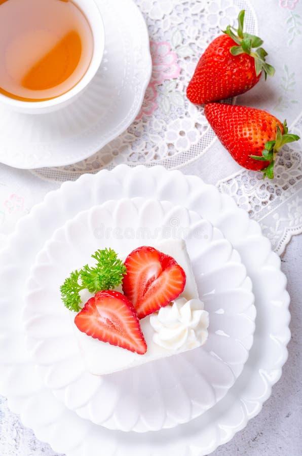 Ciasto domowe, ciasto truskawkowe z herbatą na białym talerzu i ozdobione truskawkami, co daje uczucie porannego zdjęcie royalty free