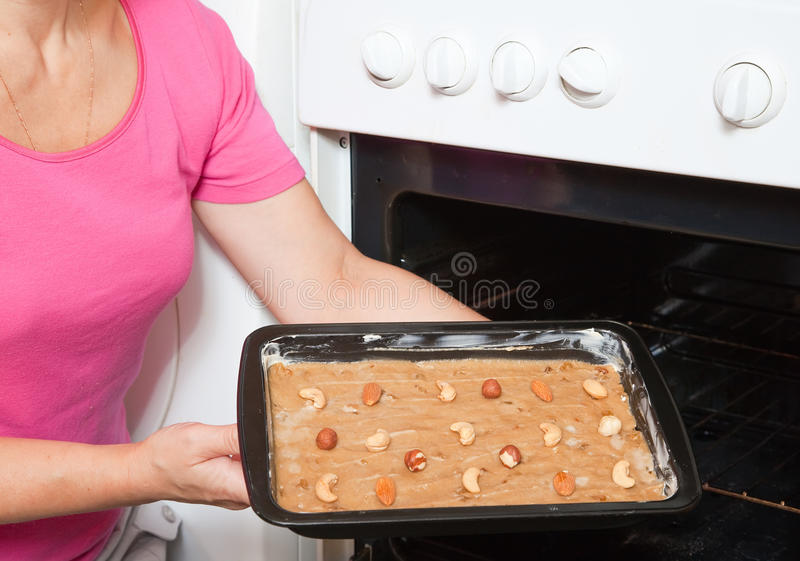 ciasto kobieta wręcza piekarnika kładzenie zdjęcia stock