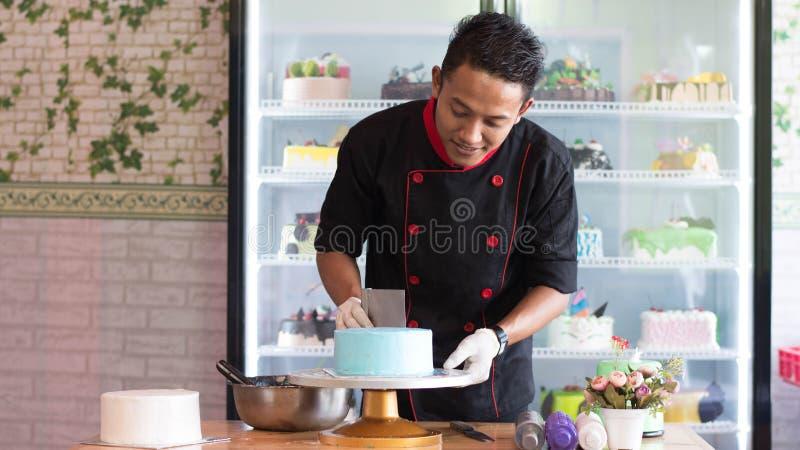 Ciasto szef kuchni dekoruje b??kita tort z ch?odziarka tortem przy kawiarni i piekarni sklepem indoors pokazuje zdjęcie stock