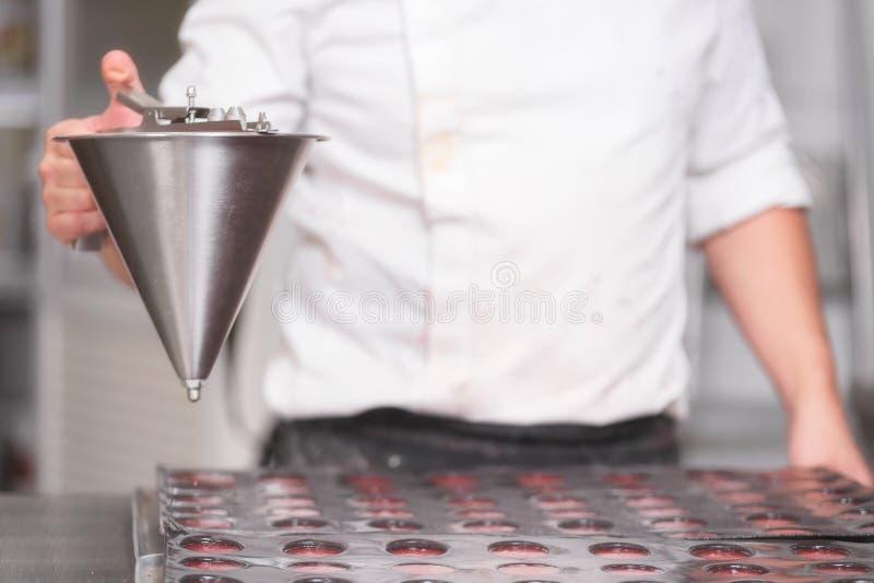Ciasto szefa kuchni dolewania truskawkowy marmoladowy, działanie przy kuchnią ciasto sklep obraz stock