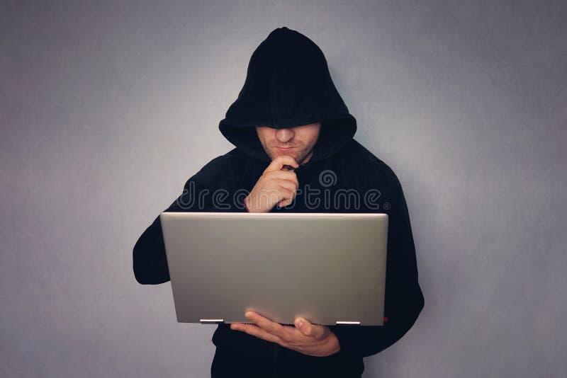 Ciberdelincuencia, el cortar y crimen de la tecnología - pirata informático de sexo masculino en sitio oscuro con el ordenador po imagenes de archivo