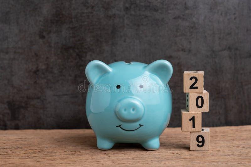 Cible économisante heureuse de l'année 2019, concept de buts de budget, d'investissement ou de finances, tirelire bleue et pile d image stock