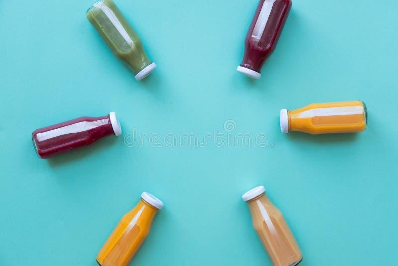 Cibo, bevande, dieta e concetto sani della disintossicazione - fine su delle bottiglie con differenti frutta o succhi di verdura immagine stock libera da diritti