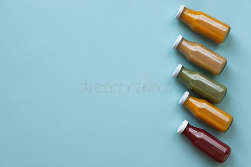 Cibo, bevande, dieta e concetto sani della disintossicazione - fine su di cinque bottiglie con differenti frutta o succhi di verd fotografia stock libera da diritti
