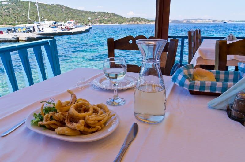Cibo del calamaro fritto e bere vino bianco in una tonalità di un taverna greco tipico fotografia stock libera da diritti