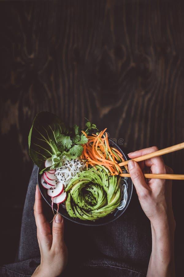 Cibo della ciotola cruda del vegano con le tagliatelle di riso, le verdure e l'avocado su fondo di legno Vista superiore con lo s fotografia stock