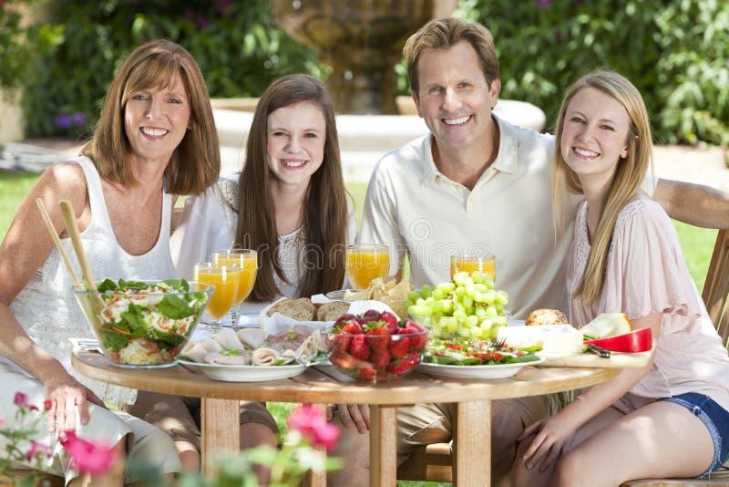 Cibo sano della famiglia dei bambini dei genitori all'esterno fotografia stock