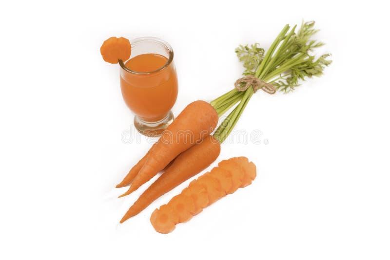 Cibo sano e concetto stante a dieta, carota e succo di carota fresco o succo sano organico in vetro isolato su fondo bianco fotografia stock libera da diritti