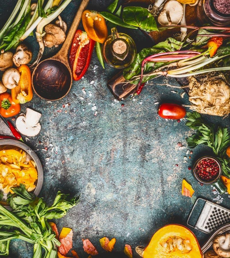 Cibo stagionale di autunno e cucinare con la zucca e gli ingredienti organici freschi delle verdure su fondo rustico, vista super fotografia stock