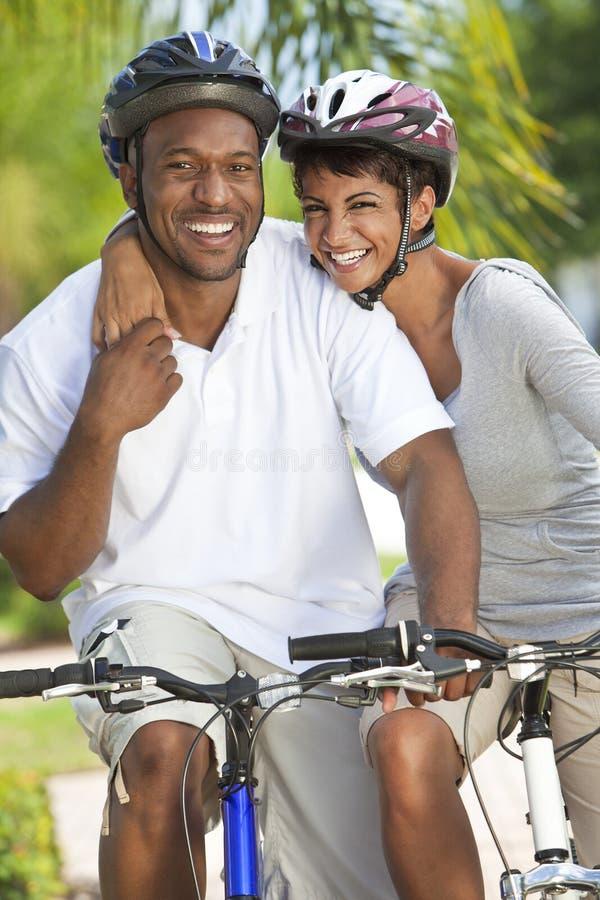 Ciclagem dos pares do homem & da mulher do americano africano imagem de stock