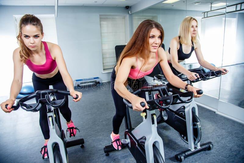 Ciclagem em bicicletas de exercício Três jovens mulheres atrativas na roupa dos esportes que exercitam no gym bicycles imagens de stock royalty free