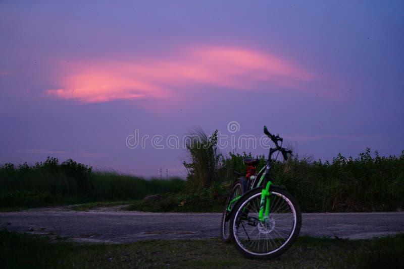 Ciclando con le nuvole rosse al tramonto immagine stock libera da diritti