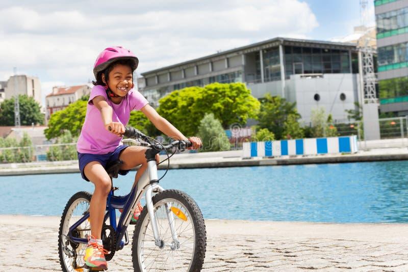Ciclismo africano feliz da menina ao longo do rio na cidade fotografia de stock royalty free