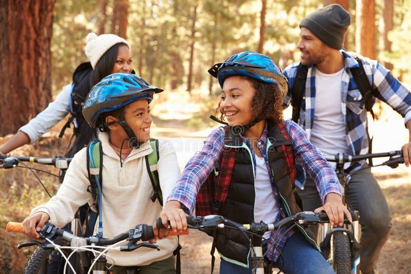 Ciclismo afro-americano da família através da floresta da queda fotografia de stock royalty free