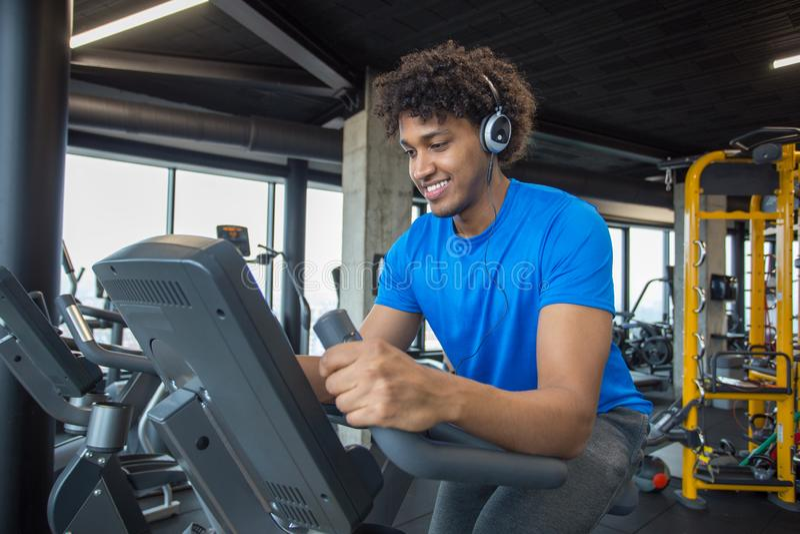 Ciclismo afro-americano novo considerável do homem no gym fotos de stock royalty free