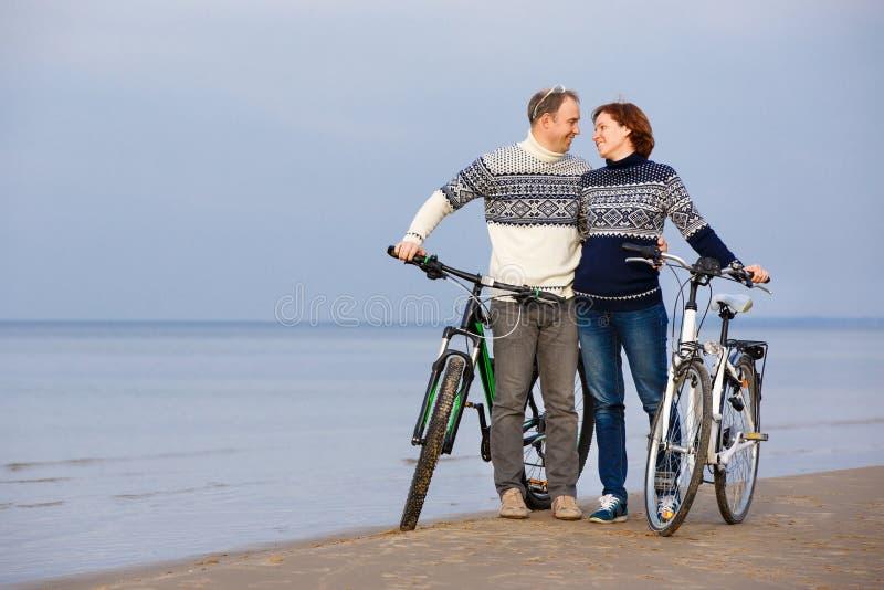 Ciclismo allegro delle coppie su una spiaggia di sabbia fotografie stock