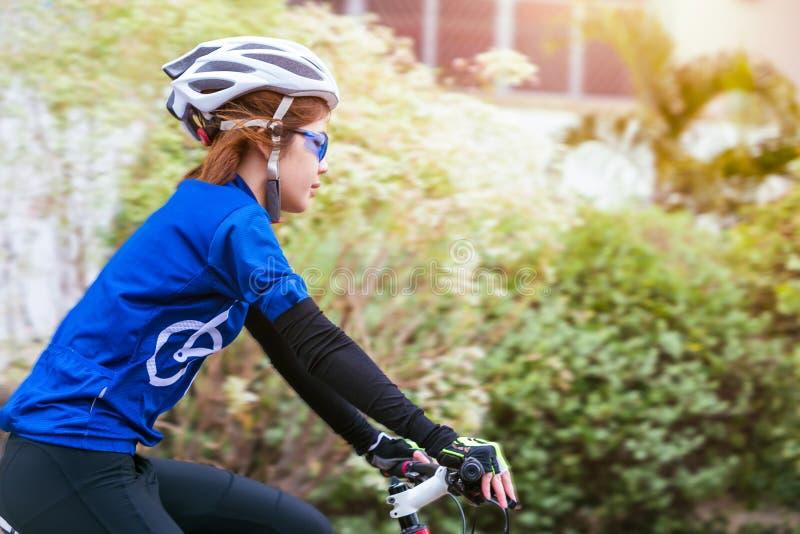Ciclismo asiático da mulher no parque Conceito saudável fotos de stock royalty free