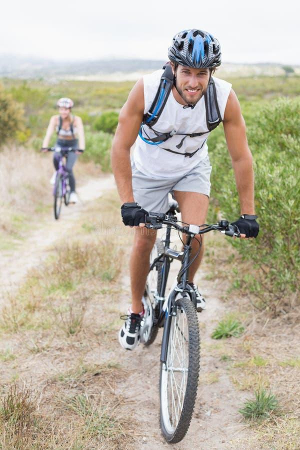 Ciclismo atrativo apto dos pares na fuga de montanha imagens de stock royalty free