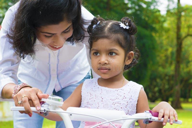 Ciclismo d'istruzione della bambina della madre immagini stock