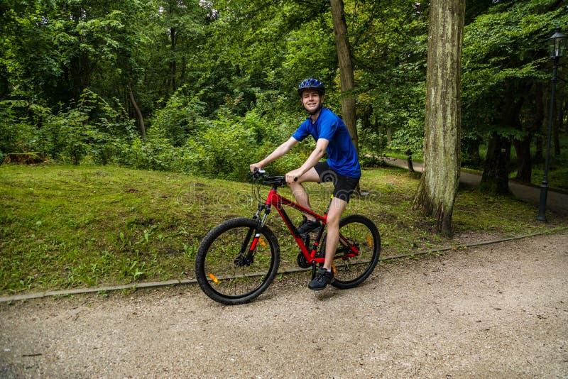 Ciclismo del giovane nel parco della città immagini stock