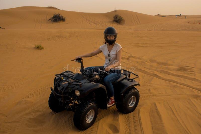 Ciclismo del quadrato del deserto Ragazza in casco che conduce una bici del quadrato immagini stock libere da diritti