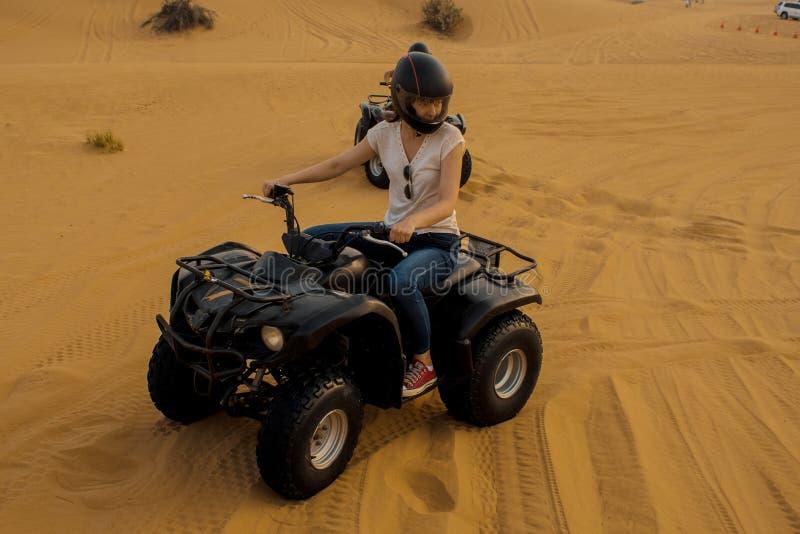 Ciclismo del quadrato del deserto Ragazza in casco che conduce una bici del quadrato fotografia stock libera da diritti