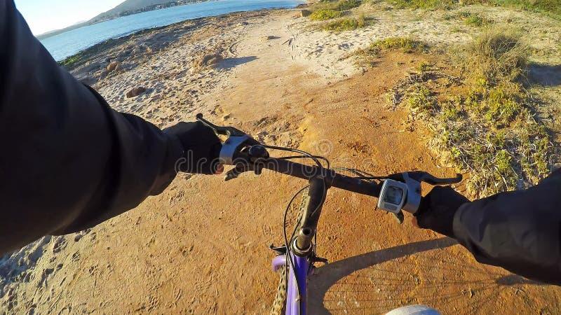 Ciclismo do homem pelo mar imagens de stock royalty free