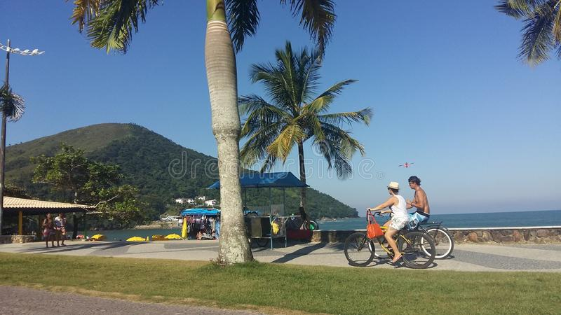Ciclismo dos pares ao longo da costa de Caraguatatuba imagem de stock royalty free