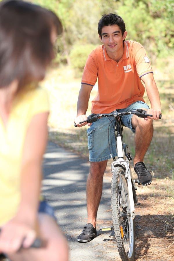 Ciclismo dos pares na floresta imagem de stock royalty free