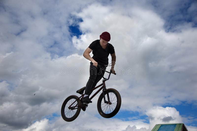Ciclismo extremo. Un adolescente en bicicleta extrema hace un truco complicado fotografía de archivo libre de regalías
