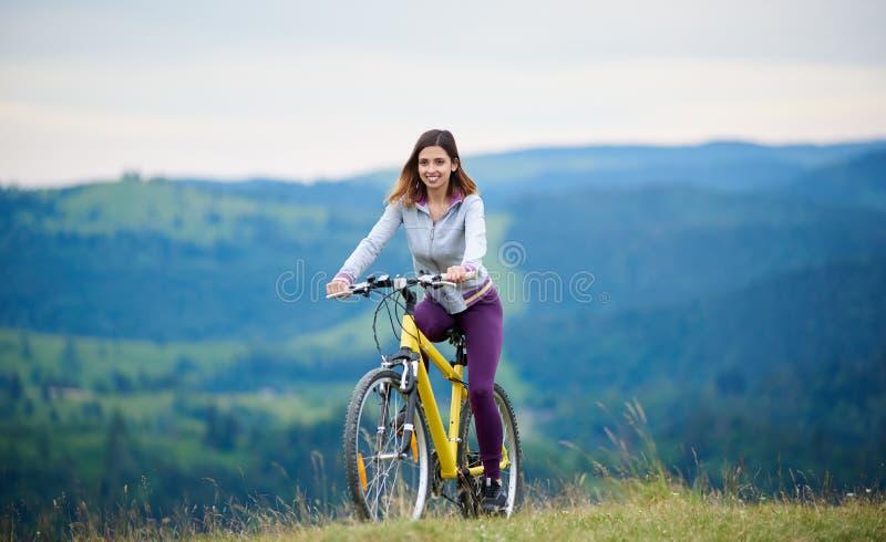 Ciclismo feliz novo da mulher no Mountain bike no dia de verão fotografia de stock